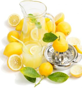 Lemon juice in pitcher and glass with citrus squeezer and fresh lemon isolated on white